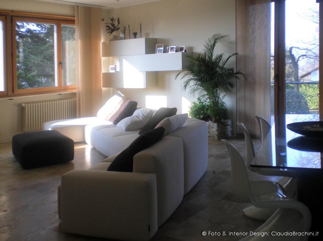 soggiorno con divano angolo e parete in geopietra